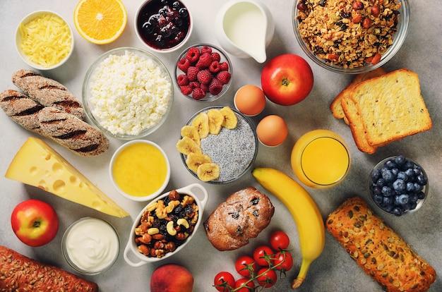 健康的な朝食食材、フードフレーム。グラノーラ、卵、ナッツ、フルーツ、ベリー、トースト、ミルク、ヨーグルト、オレンジジュース、チーズ、バナナ、アップル