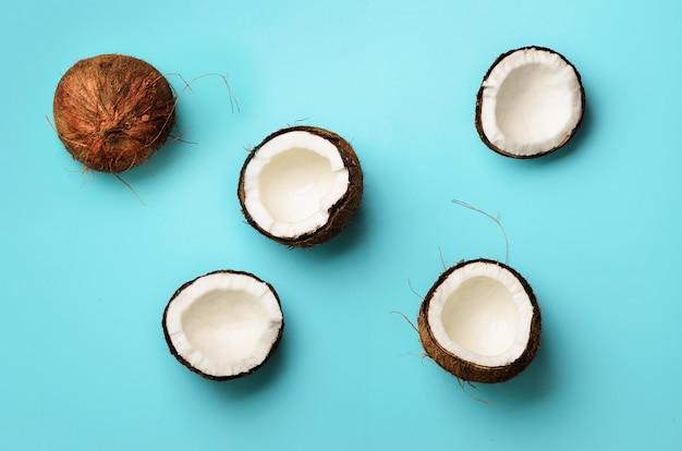 青い背景に熟したココナッツのパターン。ポップアートデザイン、創造的な夏のコンセプト。最小限のフラットレイアウトスタイルでココナッツの半分。