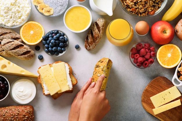 Женские руки распространяя масло на хлеб. женщина готовит завтрак. здоровый завтрак ингредиенты, еда кадр.