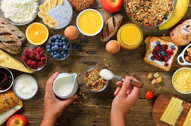 朝食 - ヨーグルト、フルーツ、ベリー、ミルク、ヨーグルト、ジュース、チーズとグラノーラを調理する女の子。きれいな食事、ダイエット、デトックス、ベジタリアン料理のコンセプト