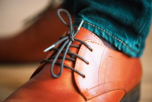 木製の寄せ木張りの床にひもで実業家茶色の革の靴。スタイルとファッションのコンセプト