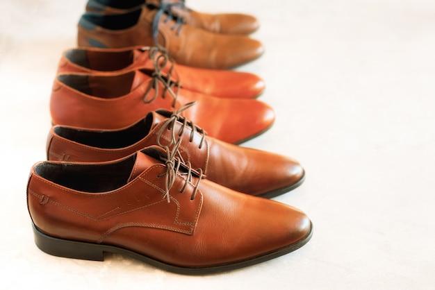 古典的なファッションは、灰色の背景に男性用の茶色の靴を磨きました。販売と買い物のコンセプトです。モデルの違う靴と茶色の色。