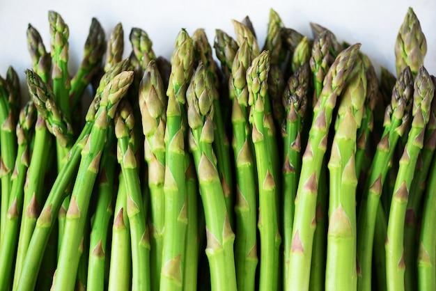 Зеленая свежая спаржа на серой предпосылке. вид сверху. сырье, веганский, вегетарианское и чистое питание концепции.
