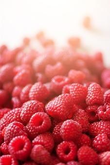 熟したラズベリーマクロ。コピースペースとフルーツの背景。日当たりの良い夏と果実の収穫の概念。日光の影響ビーガン、ベジタリアン、ローフード。