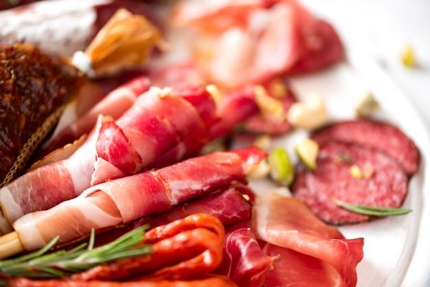 冷製スモークミートプレート。伝統的なイタリアの前菜、サラミ、生ハム、ハム、ポークチョップ、灰色の背景にオリーブのまな板。平面図、コピースペース、平干し