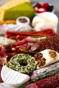 伝統的なイタリアの前菜、サラミとまな板、冷たい燻製肉、生ハム、ハム、チーズ、オリーブ、灰色の背景にケッパー。