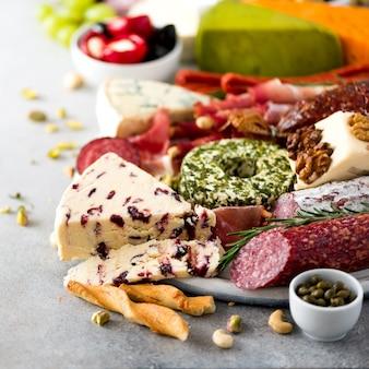 伝統的なイタリアの前菜、サラミとまな板、冷たい燻製肉、生ハム、ハム、チーズ、オリーブ、灰色の背景にケッパー。チーズと肉の前菜スクエアクロップ
