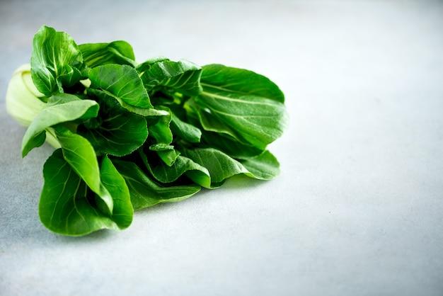 灰色のコンクリート背景に緑の有機チンゲン菜白菜。