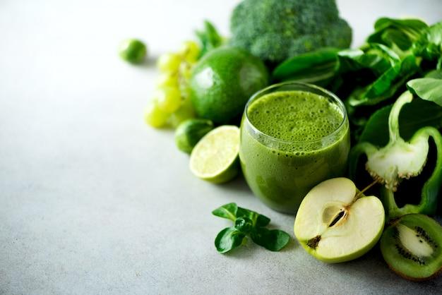 緑の健康スムージー、ケールの葉、ライム、リンゴ、キウイ、ブドウ、バナナ、アボカド、レタスとガラス。生、菜食主義者、ベジタリアン、アルカリ食品のコンセプトです。