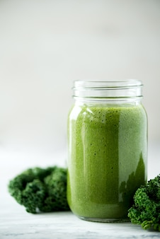 緑の健康スムージー、ケールの葉、ライム、リンゴ、キウイ、ブドウ、バナナ、アボカド、レタスとガラスの瓶マグカップ。生、菜食主義者、ベジタリアン、デトックス、アルカリ性食品のコンセプトです。