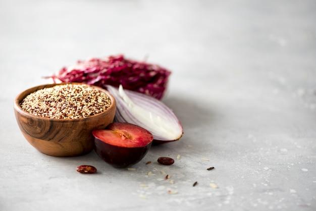 木製のボウルと灰色の背景にローズマリーの白と赤の生有機キノア。健康食品の成分コピースペース