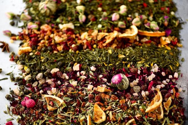 茶の背景:緑、黒、花、ハーブ、ミント、メリッサ、生姜、アップル、ローズ、ライムツリー、フルーツ、オレンジ、ハイビスカス、ラズベリー、コーンフラワー、クランベリー。