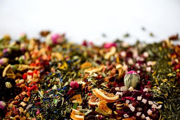 茶の背景を閉じる:緑、黒、花、ハーブ、ミント、メリッサ、生姜、アップル、ローズ、ライムツリー、フルーツ、オレンジ、ハイビスカス、ラズベリー、コーンフラワー、クランベリー。