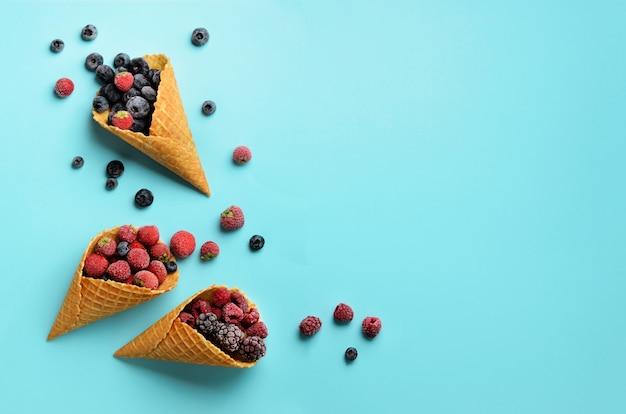 冷凍果実 - イチゴ、ブルーベリー、ブラックベリー、ラズベリーの青色の背景にワッフルコーン。