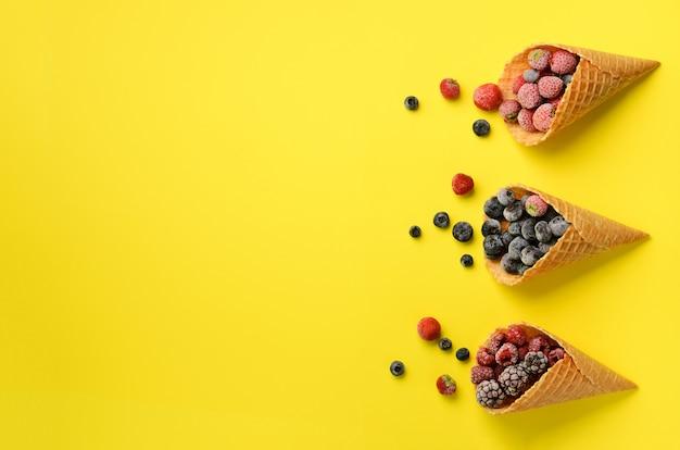 冷凍果実 - 黄色の背景にワッフルコーンのイチゴ、ブルーベリー、ブラックベリー、ラズベリー。