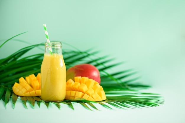 Вкусный сочный коктейль с апельсиновыми фруктами и манго. поп-арт дизайн, концепция творческого лета. свежий сок в стеклянных бутылках над зелеными пальмами листьями.