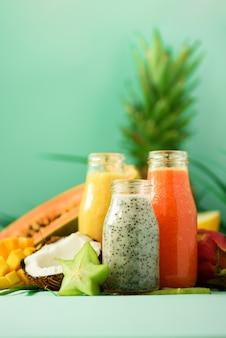 パパイヤ、ドラゴンフルーツ、パイナップル、ターコイズブルーの背景に瓶の中のマンゴーのスムージー。デトックス、ビーガンダイエット食品、健康的な食事のコンセプトです。