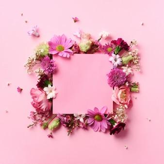 パンチの効いたパステル調の背景にピンクの花のフレーム。バレンタインデー、女性の日のコンセプト