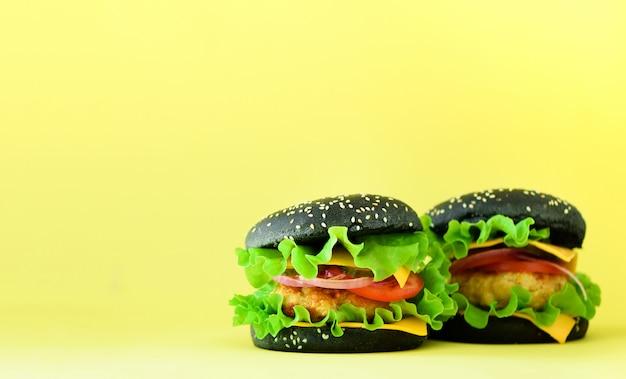 ファーストフードのフレーム。黄色の背景においしい肉ハンバーガー。食事を奪う。コピースペースで不健康な食事療法の概念