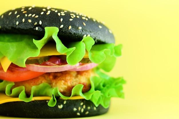 黄色の背景に牛肉、チーズ、レタス、玉ねぎ、トマトのおいしい黒バーガーのマクロの表示。不健康な食事の概念とコピースペース