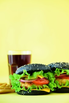 おいしいブラックバーガーやハンバーガーにフライドポテトを添えて。朝食、昼食のためのファーストフード。