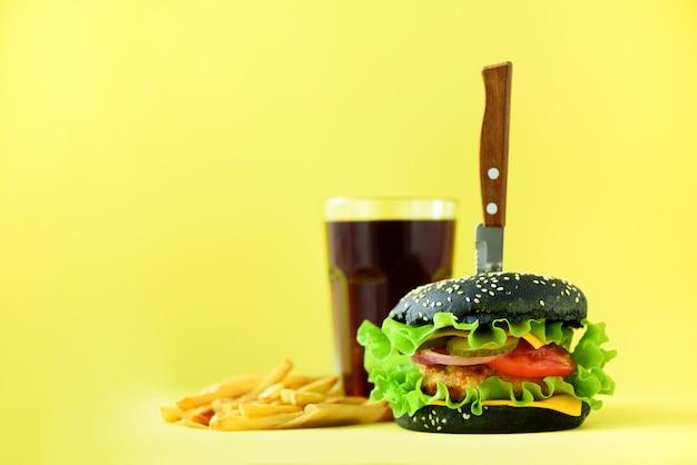 ファーストフードのバナー。チーズ、黄色の背景にレタスとジューシーな肉ハンバーガー。食事を奪う。コピースペースで不健康な食事療法の概念