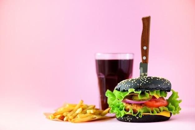 ファーストフードのバナー。チーズ、ピンクの背景のレタスとジューシーな肉ハンバーガー。食事を奪う。コピースペースで不健康な食事療法の概念