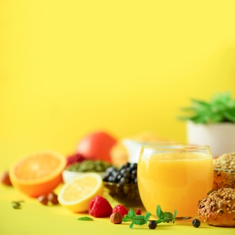 Апельсиновый сок, свежие ягоды, молоко, йогурт, вареное яйцо, орехи, фрукты, банан, персик на завтрак. концепция здорового питания.
