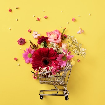 黄色のパンチの効いたパステル調の背景に花が付いているショッピングトロリー。