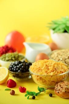 Кукурузные хлопья, мюсли, молоко, ягоды, апельсиновый сок, йогурт, вареное яйцо, орехи, фрукты, банан, персик на завтрак. вегетарианская и вегетарианская концепция.