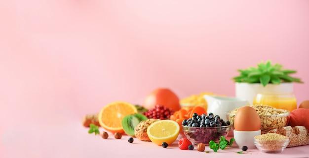 健康的な朝食食材、フードフレーム。コーンフレーク、コーンフレーク、卵、ナッツ、フルーツ、ベリー、トースト、ミルク、ヨーグルト、オレンジ、バナナ、ピーチ