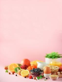 朝食は、柔らかいゆで卵、コーンフレーク、ナッツ、フルーツ、ベリー、ミルク、ヨーグルト、オレンジ、バナナ、ピンクの背景のピーチを添えています。健康食品ダイエット
