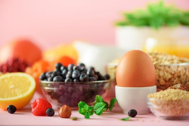 おいしい朝食用食材。半熟卵、コーンフレーク、ナッツ、フルーツ、ベリー、ミルク、ヨーグルト、オレンジ、バナナ、ピンクの背景の桃。