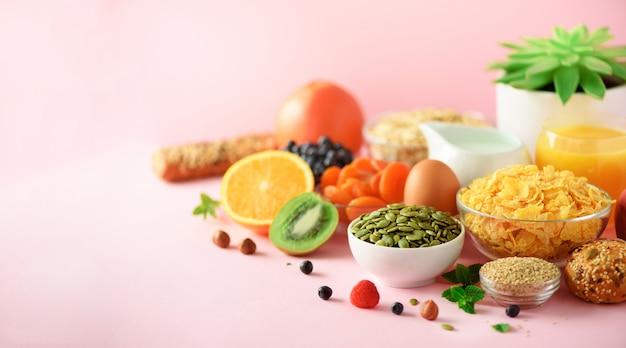 ベジタリアンの朝食半熟卵、コーンフレーク、ナッツ、フルーツ、ベリー、ミルク、ヨーグルト、オレンジ、バナナ、ピンクの背景の桃。健康食品ダイエットスペースをコピーします。バナー