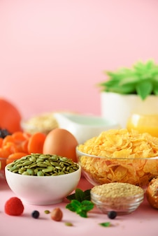 コーンフレークミルク、新鮮な果実、ヨーグルト、ゆで卵、ナッツ、フルーツ、オレンジ、バナナ、黄色の背景に朝食用ピーチ。スペースをコピーします。健康食品のコンセプトです。