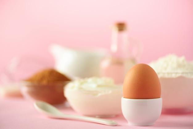 ピンクの背景に白の調理器具。食品成分。卵のマクロケーキを調理し、パンを焼くコンセプト。スペースをコピーします。