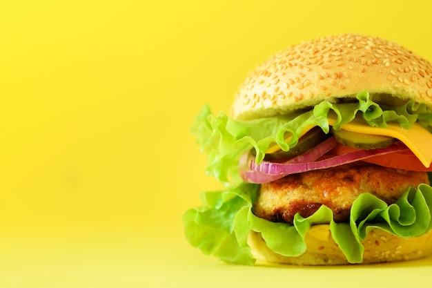 黄色の背景に牛肉、チーズ、レタス、玉ねぎ、トマトのおいしいハンバーガーのマクロの表示。バナーを閉じます。不健康な食事の概念とコピースペース
