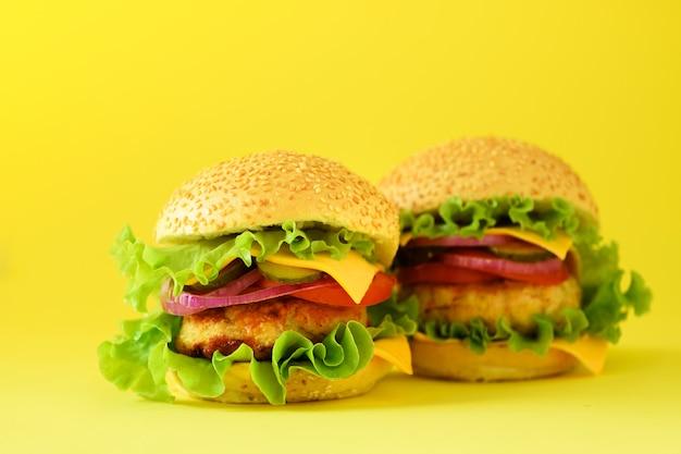 ファーストフード - ジューシーなハンバーガー、フライドポテトとコーラは黄色の背景に飲みます。食事を奪う。不健康な食事のコンセプト