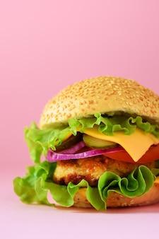 Взгляд макроса вкусного бургера с говядиной, сыром, салатом, луком, томатами на желтой предпосылке. закройте баннер. концепция нездоровой диеты и копией пространства