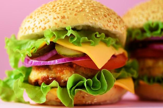 Взгляд макроса вкусного бургера с говядиной, сыром, салатом, луком, томатами. концепция нездоровой диеты и копией пространства