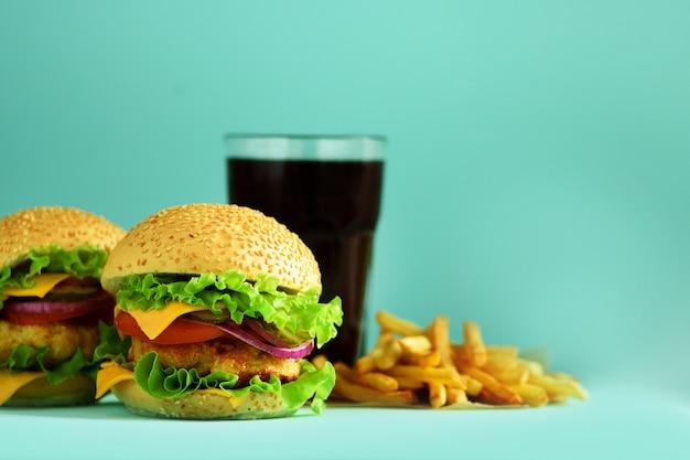 ファーストフード - ジューシーなハンバーガー、フライドポテトとコーラは青い背景に飲みます。食事を奪う。コピースペースで不健康な食事療法の概念