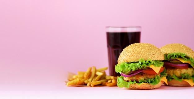ファーストフードのバナー。ジューシーな肉ハンバーガー、フライドポテトとコーラはピンクの背景に飲みます。食事を奪う。不健康な食事のコンセプト
