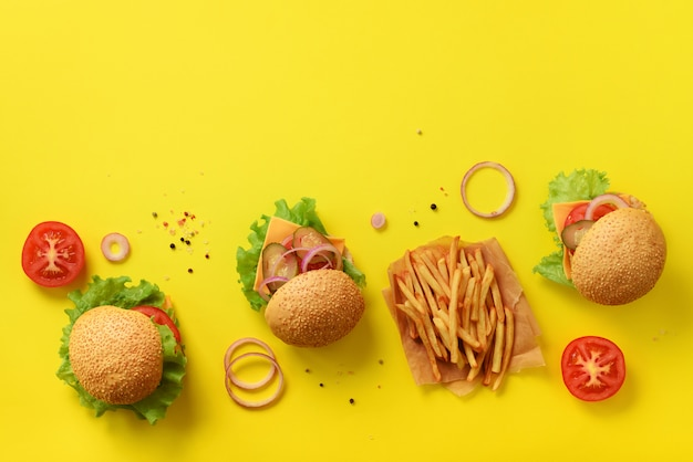 ファーストフードのバナー。牛肉、トマト、チーズ、玉ねぎ、キュウリ、黄色の背景にレタスのジューシーな肉ハンバーガー。