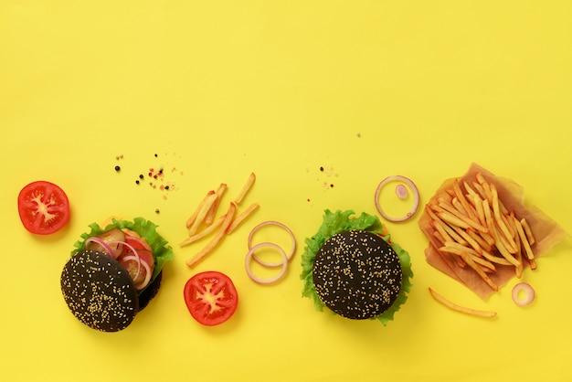 牛肉、トマト、チーズ、玉ねぎ、キュウリ、レタスと黒のハンバーガー。ファーストフードのバナー。食事を奪う。不健康な食事のコンセプト