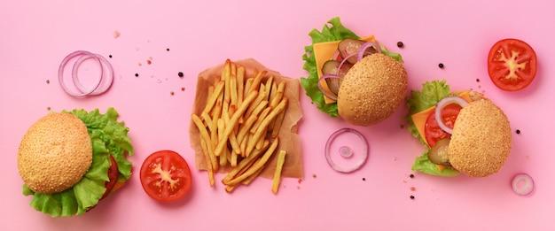 ファーストフードのバナー。牛肉、トマト、チーズ、玉ねぎ、キュウリ、ピンクの背景のレタスとジューシーな肉ハンバーガー。