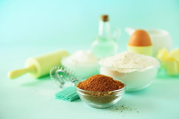Различные ингредиенты для выпечки - масло, сахар, мука, молоко, яйца, масло, ложка, скалка, щетка, венчик