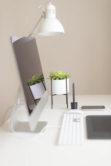 デザイナーワークスペースミニマルな本社。空白の画面のデスクトップコンピューター