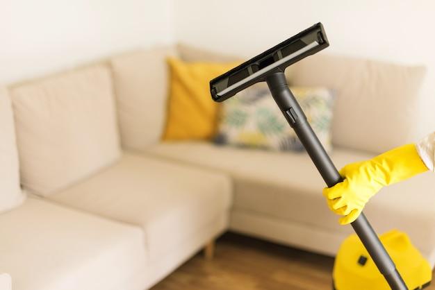 Софа чистки женщины с желтым пылесосом. чистая концепция