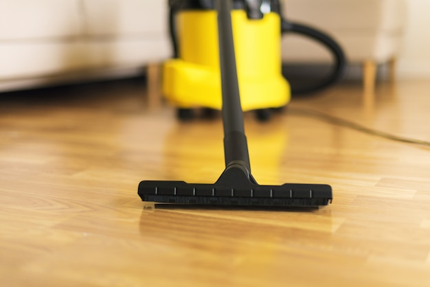 黄色い掃除機でリビングルームを掃除する保護手袋の女。