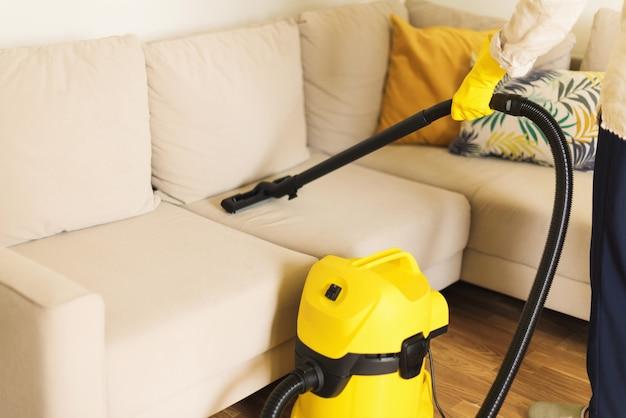 黄色い掃除機でソファを掃除する女性。きれいなコンセプト